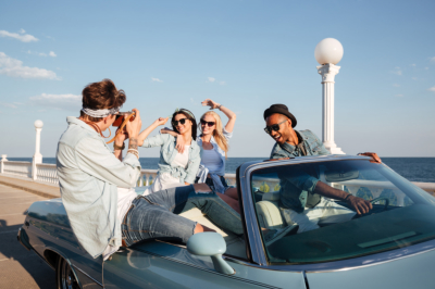 Group of young people taking picture on a car